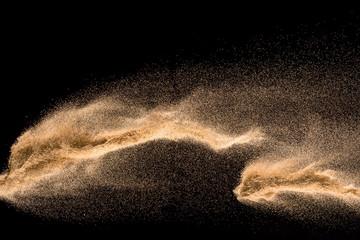 Dry river sand explosion. Golden colored sand splash against  black background.