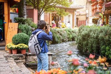 Young traveler walking and photographing at lijiang old town in Yunnan province, China