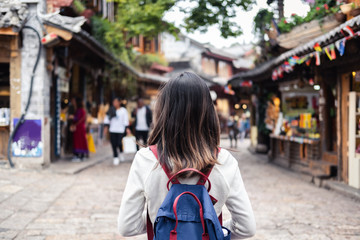 Young woman traveler walking at lijiang old town in Yunnan province, China