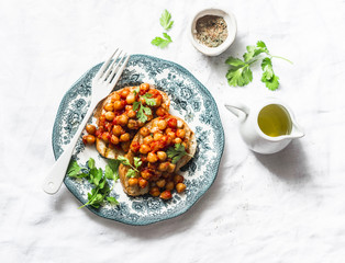 Spicy chickpeas in tomato sauce toast - delicious snack on a light background, top view