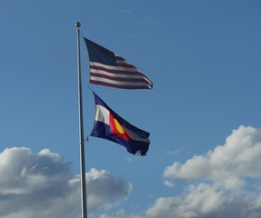 US and Colorado state flags waving in the wind from one pole, with white fluffy clouds in the background