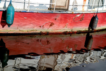 Red ship with a rusty hull and peeling paint is reflected in the calm water in Amsterdam, Netherlands. Selective focus