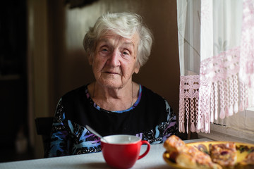 An elderly woman has Breakfast sitting at home.