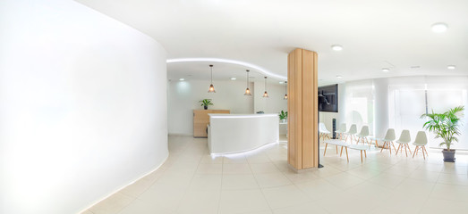 Panorama of a bright reception and waiting room in a clinic with desk, modern chairs and plants. Indoor mockup with screen with copy space. Wall mural
