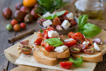 Italian bruschetta with chopped tomatoes, basil, feta cheese and olive oil. Fresh homemade caprese bruschetta