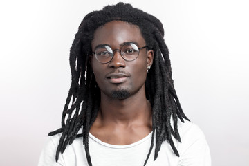 Handsome muscular black man with dreadlocks wearing glasses looking camera on white backgound