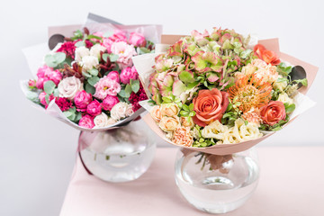 two beautiful spring bouquet. flowers arrangements with various of colors in glass vase on pink table. bright room, white wall