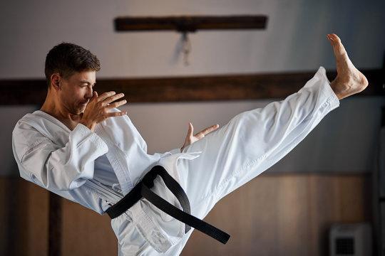 Man in kimono doing karate kick