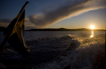 Swedish flag on a ferry in lake Mälaren at sunset in Stockholm