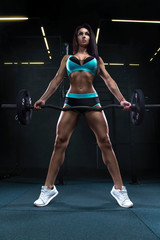 Sexy fitness brunette woman is doing biceps curls with barbell in the gym