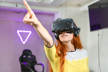 A young and very beautiful girl, with red hair, in a yellow sweater, plays games of virtual reality