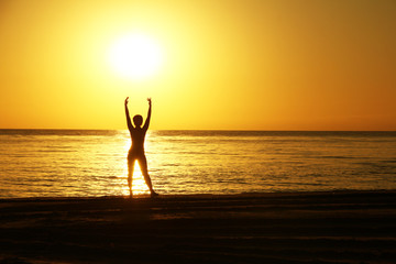 Silhouettes of the woman with the raised hands against a background of a sunrise on the sea coast.
