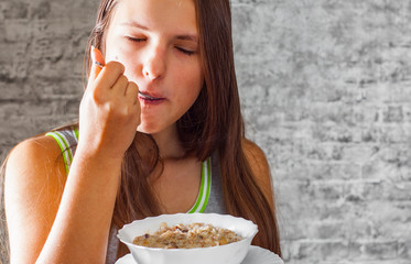 portrait of young teenager brunette girl with long hair eating muesli on gray wall background