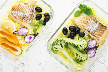 A healthy meal for a snack is a lunch box. Glass containers with fresh steam sea fish, rice with turmeric, fresh vegetables, olives, broccoli. Top View.