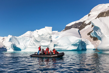 Spoed Foto op Canvas Antarctica Boat full of tourists explore huge icebergs drifting in the bay