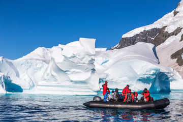 Poster de jardin Antarctique Boat full of tourists explore huge icebergs drifting in the bay