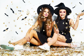 portrait of two happy young women in black witch halloween costumes on party over white background with bats . firecrackers in the background. confetti . the concept of Halloween . funny faces.