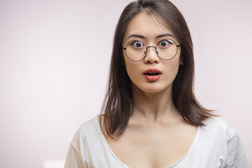 Shocked surprised Asian woman in optical eyewear, looking with unbelieving, terrifying expression or surprise. She is shocked with information.