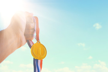 man hand raised, holding gold medal against sky. award and victory concept.