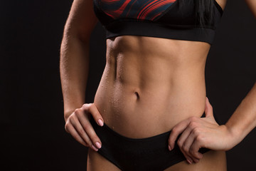 Inrecognizable sportswoman showing off her perfect muscular ripped abs, close up. Fitness model. Perfect Slim Body. Isolated indoor shot gainst black wall.