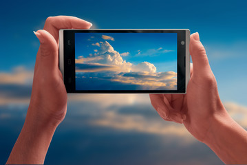 Beautiful blue sky on a screen of smartphone
