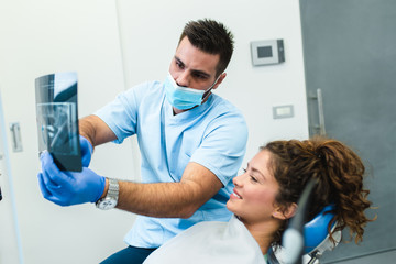 Handsome smiling dentist looking at x-ray image of his beautiful young woman patient.
