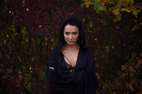 Young woman in the black cloak in the autumn forest