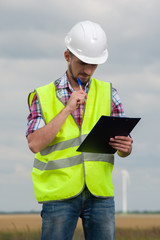 Young male engineer in green vest and helmet