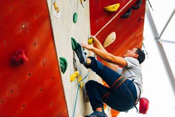 Muscular man practicing rock-climbing on a rock wall