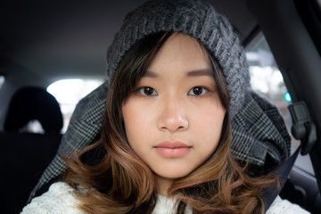 Pretty young woman takes a selfie in the car