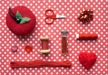 Red Sewing kit accessories and equipment for sewing and Needlework. Various tools for needlework: pin cushion for needles, threads, scissors, buttons, beads and thread heart. Flat lay, top view