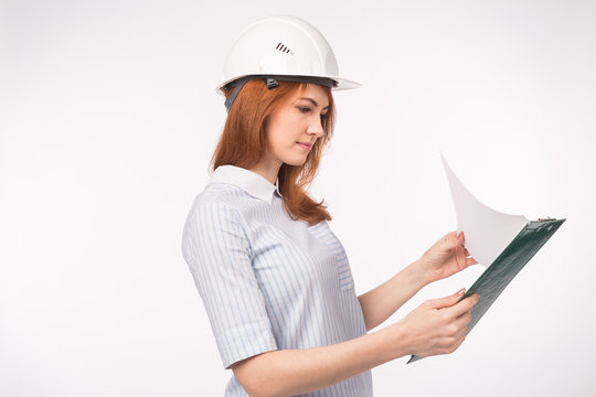 Architect, worker and realtor concept - woman builder or engineer with documents on white background with copy space
