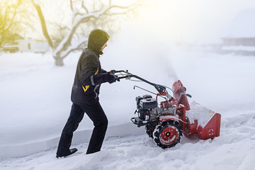 young man removes snow with a snowplower