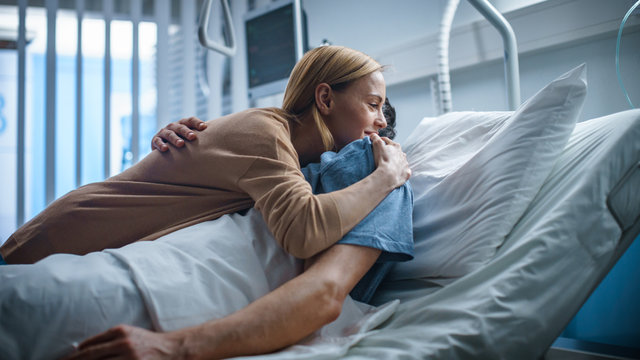 In the Hospital, Happy Wife Visits Her Recovering Husband who is Lying on the Bed. They Lovingly Embrace and Smile.