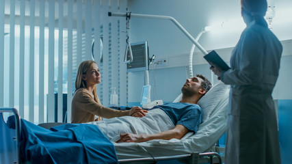 In the Hospital, Patient Lying in Bed, his Wife Listens to Doctor's Explanation about Sick Man's Condition. Sickness, Suffering and Death Themes. Loved Ones with a Hope.