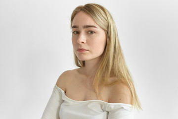 Close up portrait of gorgeous young woman with straight fair hair, green eyes and pure skin with freckles looking at camera, showing her bare shoulders. Natural beauty, femininity, style and fashion