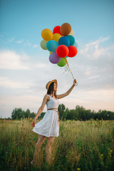 Smiling woman with balloons walking in green field