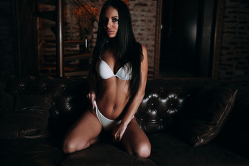 Sexy brunette in white lingerie.Sexy girl on a leather couch