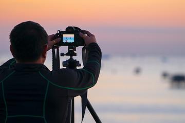 photographer adjust focus of landscape photo on screen of camera, using focus technology