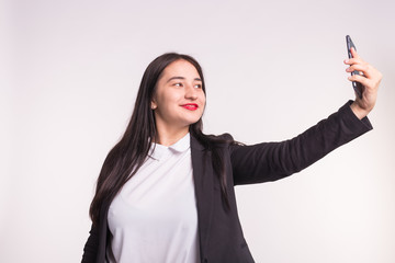 Technology, smartphone and people concept - Happy young asian woman making selfie over white background