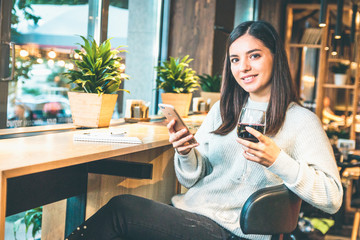 Christmas concept - Happy young woman with glass of wine or glintwine checking the phone