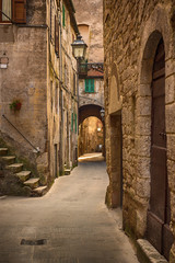 Fototapeten Schmale Gasse Narrow street of medieval ancient tuff city Pitigliano, travel Italy background