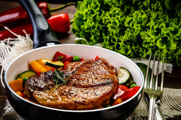 Grilled steak with vegetables in pan on wooden table