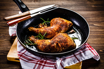 Fried chicken legs in pan on wooden table
