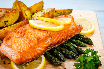 Grilled salmon with baked potatoes, asparagus and vegetable salad
