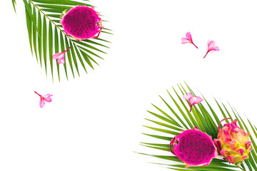 Tropical composition with dragon fruits, exotic pink flowers and palm leaves on white background. Flat lay, top view.