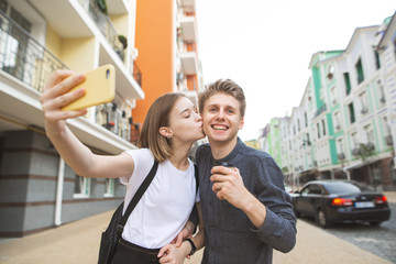 Portrait of a happy young couple: girl kisses her boyfriend in a cheek and takes a selfie on a smartphone, young man smiles with a cup of coffee in her hands.Couple take selfie background of the town
