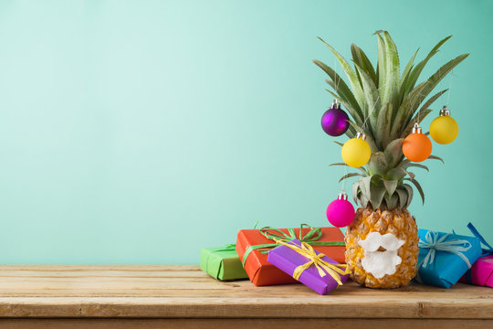 Christmas holiday concept with  pineapple as alternative Christmas tree and gift boxes
