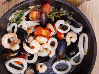 Fried seafood with tomatoes in a frying pan