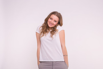 Young blonde woman standing with hands in pockets wearing white shirt on white background